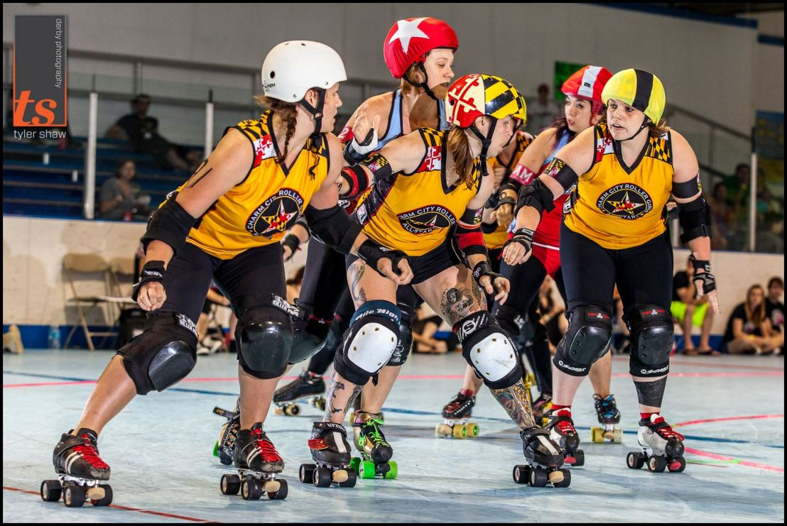 Holly Go Hardly doesn't need to snap her head back & forth to know where her opponent is. She keeps her head steady, and sits on her opponent to feel her movement. Notice how the inside & outside line blockers are looking? Wonderful! Photo by Tyler Shaw - Prints Charming Derby Photography